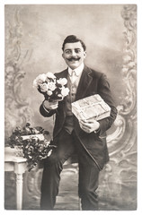 portrait of young man with rose flowers and gift