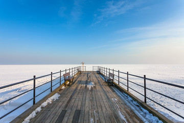Wooden pier on the frozen sea