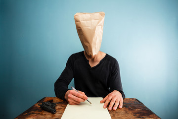 Man with bag over head writing suicide note