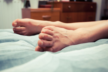 Feet of young woman on bed at home