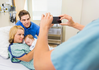 Nurse Photographing Couple With Newborn Baby Through Mobilephone