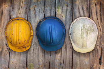 Three vintage construction helmets on a wooden wall
