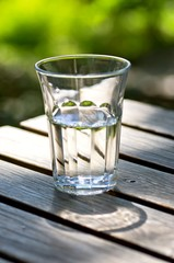 Glass of fresh water on a table outdoors.
