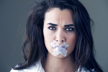 Young woman silenced with a masking tape