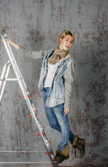 girl in jeans standing on a stepladder
