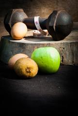 eggs , kiwi , measuring type , apple and dumbbells for training