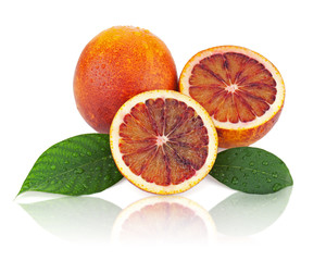 Blood oranges with cut and green leaves isolated on white backgr