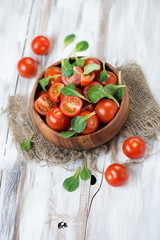 Fresh cherry tomatoes and corn salad over wooden background
