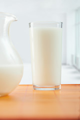 glass of milk and pitcher on table