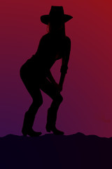 Cowgirl silhouette squatting down on a hilltop