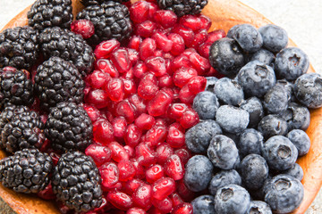 Closeup of juicy mixed berries in a wooden bowl