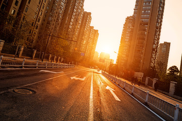 Fotomurales - road and buildings at city with sunset