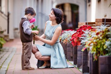 Little boy giving flower to his mom