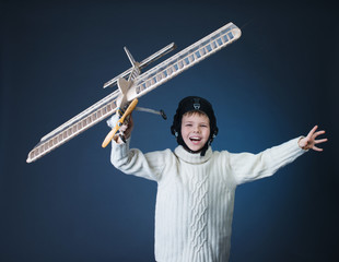 Smiling boy playing with a wooden airplane model