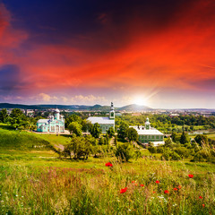 red poppy flowers and the green monastery at sunset