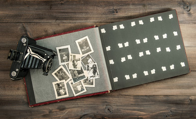 camera and album with old photos on wooden table