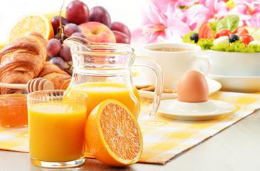 Breakfast with coffee, orange juice, croissant, egg, vegetables
