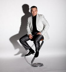 man in suit sitting on bar chair against white background