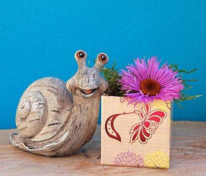 Lustige Schnecke mit Geschenk und Blume