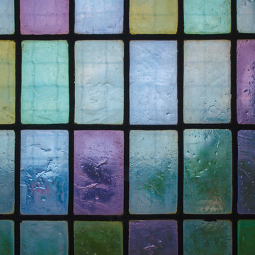 colored stained glass window with block pattern blue green tone