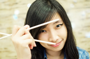 Asian young woman holding chopsticks