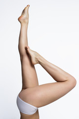 Waxing woman smooth legs pointing up on a white background