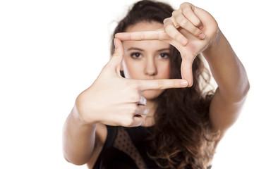 beautiful girl looking through fingers frame