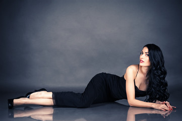 beautiful seductive woman in black dress lying on the floor