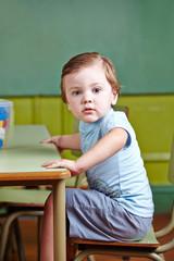 Kleiner Junge sitzt im Kindergarten am Tisch