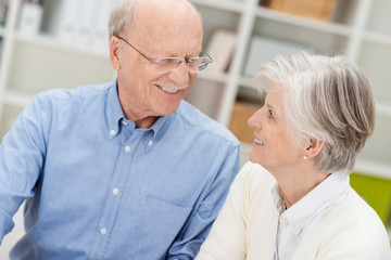 senioren-ehepaar schaut sich lächelnd an