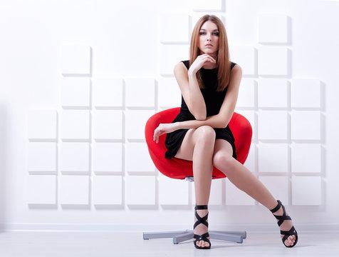 Sexy woman sitting on a chair. Fashion shot