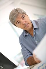 Senior businessman sitting in front of desktop