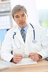Doctor in office writing medical prescription
