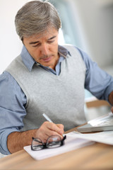 Senior man in office writing on paper
