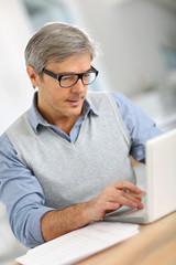 Senior businessman in office working on laptop
