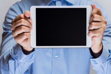 Man in blue shirt holding white tablet pc