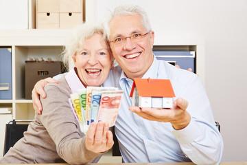 Happy elderly couple with Euro money and house