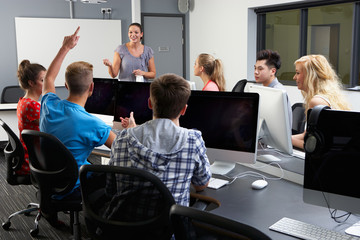 Group Of Students With Female Tutor In Computer Class