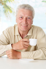 Old man drinking coffee at table