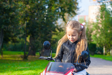 Adorable happy little girl in leather jacket sitting on her toy
