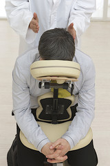 Businessman sitting on massage chair, getting shoulder massage.