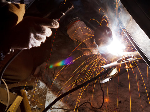 car repairs by welding in field at night