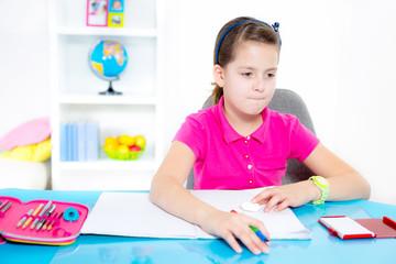 Smiling Caucasian girl doing homework at home.