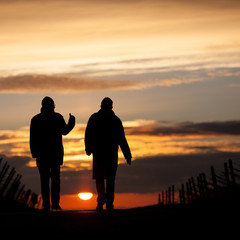two silhouetted seniors walking in sunset