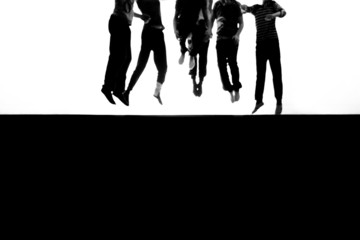 defocused legs of teenagers jumping in background