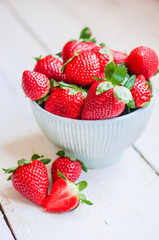 Closeup of strawberries in a bowl on wooden backgorund