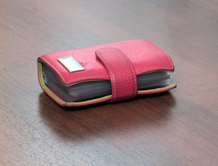 red case for visiting cards isolated on wooden desk background