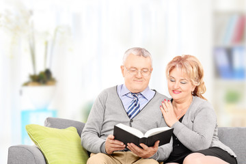Mature couple reading a book seated on couch, at home