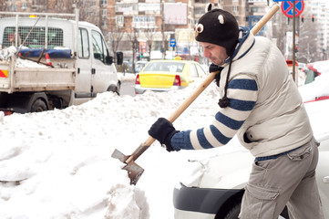 Man cleaning the snow with a shovel near his car