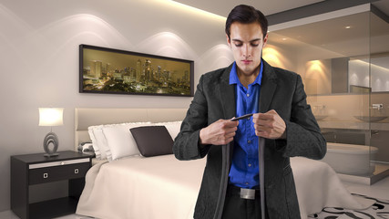 young male businessman getting dressed for work in a hotel.